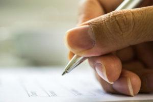Man's Hand Filling application form