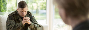 PTSD Header Image of soldier sitting on couch holding hands together