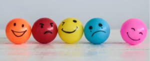 a line of different colored balls, each with a drawn on face representing different emotions.